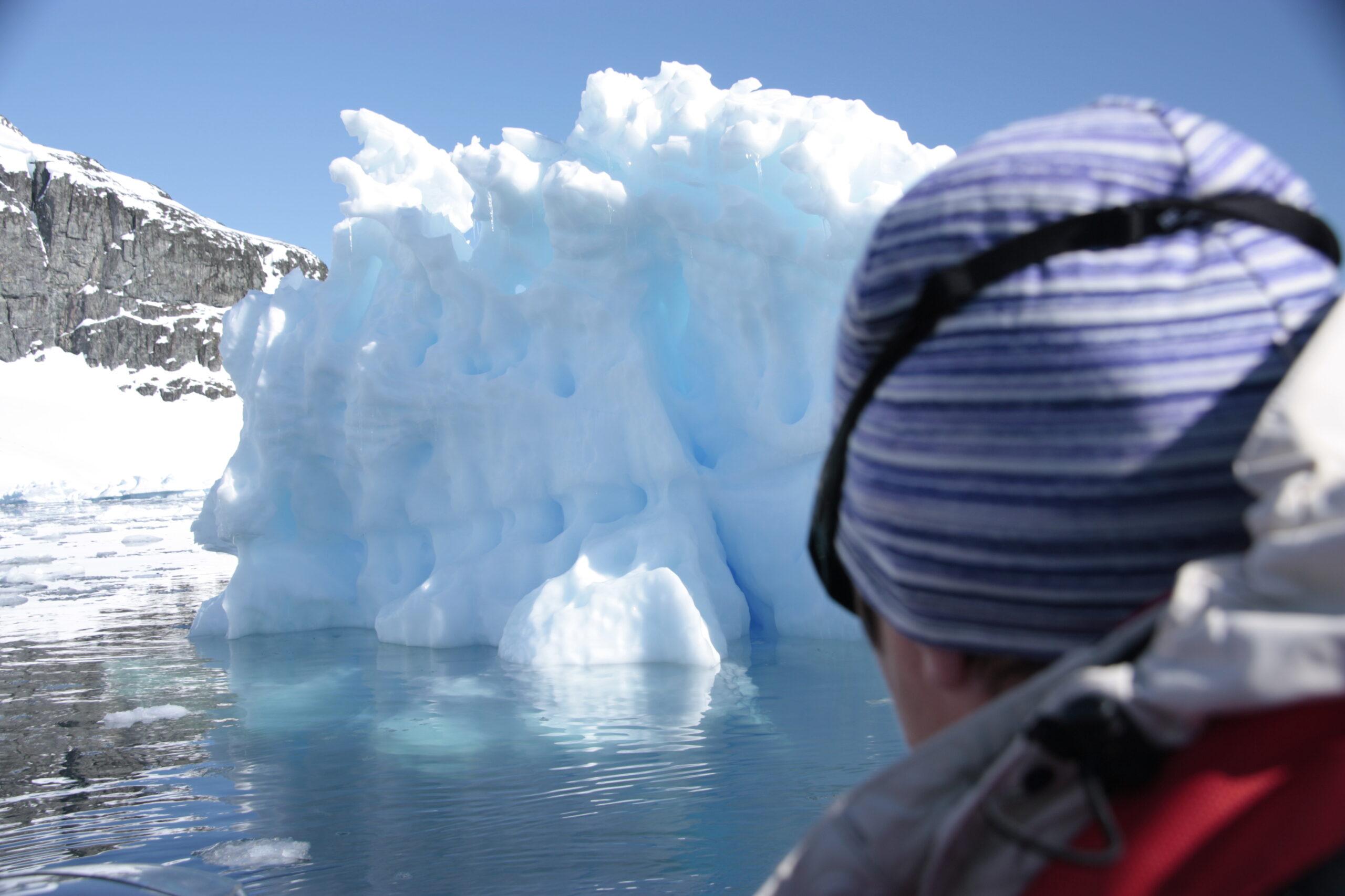 Persoon kijkend naar ijsberg op Antartica